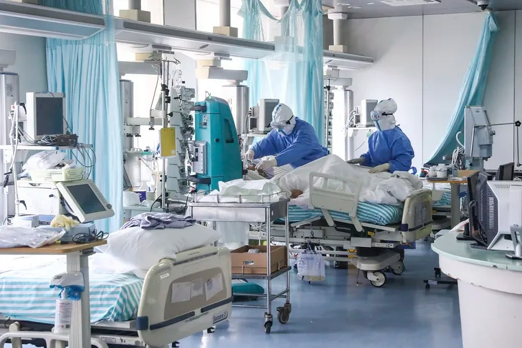 In this Feb. 13, 2020 photo released by China's Xinhua News Agency, nurses in protective suits treat a patient in the intensive care unit at Ditan Hospital in Beijing.