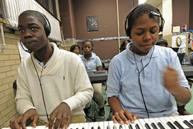 At Tilden Middle School in Philadelphia, Alandra Abrams teaches keyboard to seventh graders on Nov. 7, 2012.  Here, students Anthony Gamble, left; and Wakeer Murray, both 12 years old.  APRIL SAUL / Staff Photographer