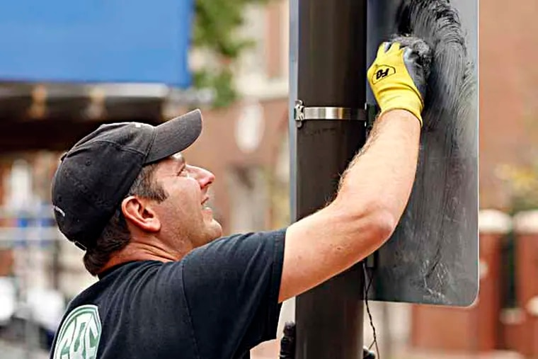 Todd Kelley, Founder & President of Graffiti Removal Experts cleans a sign on the corner of 3rd and Walnut streets in Philadelphia on October 9, 2013. ( DAVID MAIALETTI / Staff Photographer )