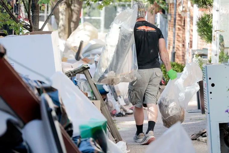 On South Taney Street in Center City Philadelphia Saturday, Servpro Society Hill employees haul away items ruined by flooding from the remnants of Hurricane Ida. On Sunday, the city issued a list of resources for storm victims and safety warnings.
