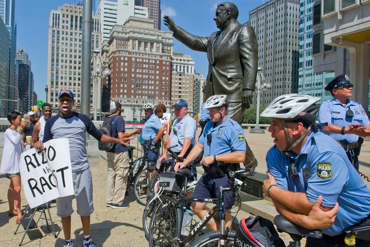 Black Lives Matter member Asa Khalif berates officers after a Klan hood he placed atop the head of the Frank Rizzo statue was removed outside the Municipal Services Building.