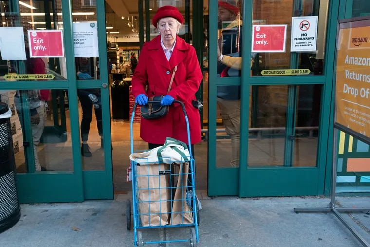 A woman who does not mind her photograph being published, but who prefers not to have her name in the paper, exits the Whole Foods Market on South Street in Philadelphia, March 18, 2020. Whole Foods Market has instituted Senior citizen only shopping from 7:30-8 a.m. each morning. The store hours are now: Senior citizen shopping 7:30-8 a.m. the store is open to the general public 8 a.m.-8 p.m, the early close is for cleaning and restocking.