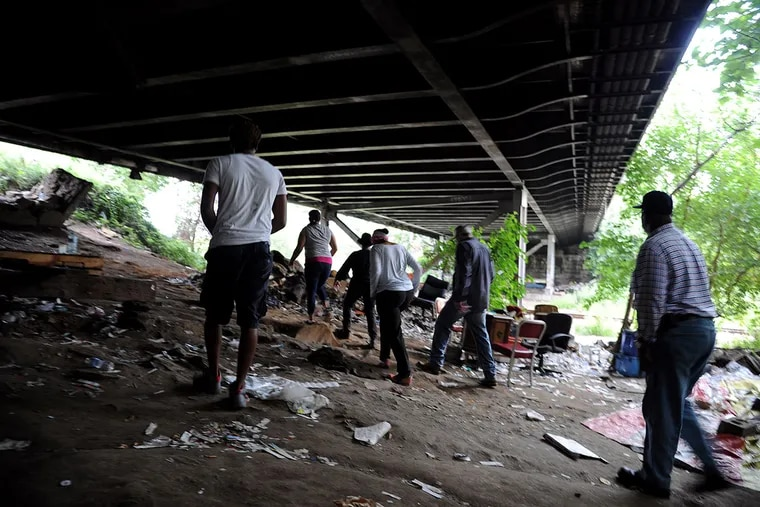 """Charito Morales, a registered nurse and advocate, leads a group through """"El Campamento,"""" a camp of homeless drug users under a railroad bridge in Fairhill. (TOM GRALISH / Staff Photographer)"""