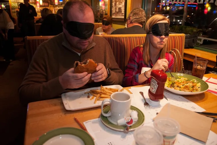 From left, Craig Westphal and Jenny Westphal wear eye masks to experience what it is like to eat food without sight Monday at Applebee's.