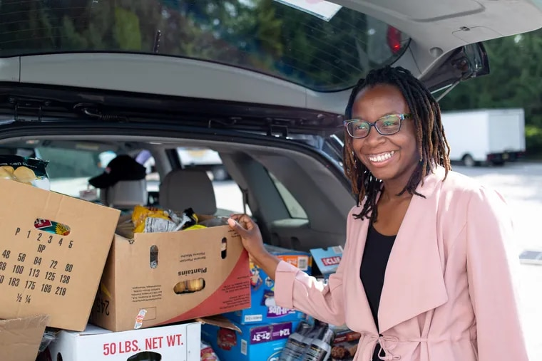 Shontae Smarr, director of Philly Food Rescue, outside Fresh Grocer in Wyncote with a car full of groceries that will be donated to people in Kensington.