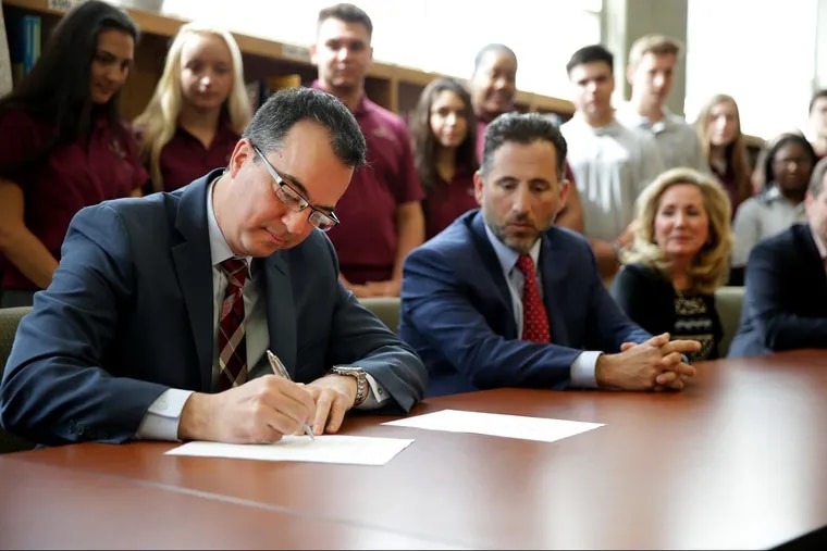 Founding board member Peter Sciortino, left, signs the lease at Holy Cross Academy in Delran, NJ on May 1, 2018. Officials with the Holy Cross Academy and the Diocese of Trenton hold a news conference to a sign a lease turning over the school to its new operators: an alumni board comprised of business leaders beginning July 1. Earlier this year, the Diocese announced plans to close the only Roman Catholic High School in Burlington County.