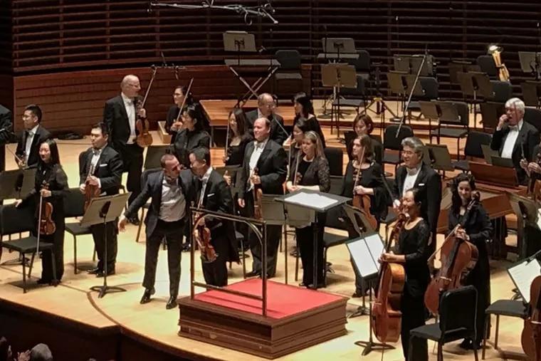 Violinist David Kim bows with Yannick Nezet-Seguin Thursday at the Philadelphia Orchestra.