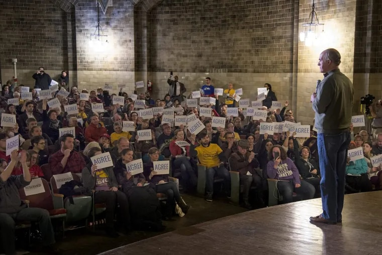"""Sen. Bob Casey hosts a town hall at the Univ. of Penn. March 12, 2017. His staff had supplied signs for the audience reading """"agree"""" on one side and """"disagree"""" on the other. TOM GRALISH / Staff Photographer"""