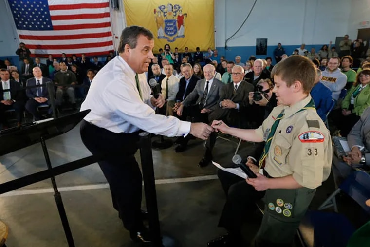 New Jersey Gov. Chris Christie hands his ink pen to Zachary Seemar, 12, of Brick, N.J., so the Boy Scout could write his family's information for the governor during a town hall meeting Tuesday, March 17, 2015, in Freehold, N.J. Seemar told Christie that his family is still suffering from the effects of Superstorm Sandy and he asked for the governor's help. (AP Photo/Mel Evans)