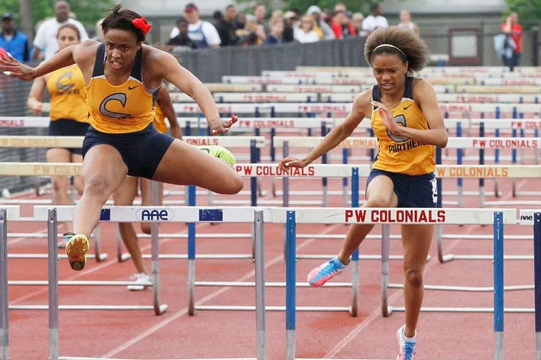 Cheltenham's Kayla Coley clears the last hurdle on her way to a record-setting win in the 100-meter hurdles in the Suburban One American meet.