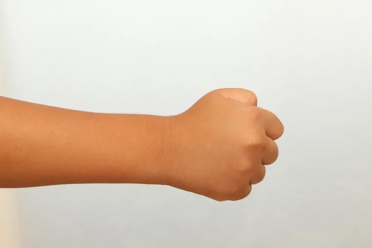 Child's fist, white background