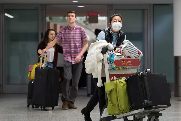 A woman wears a mask following the outbreak of the coronavirus as people arrive from the International terminal at Toronto Pearson International Airport in Toronto on Saturday, Jan. 25, 2020. A Toronto hospital said Saturday it has a confirmed case of the deadly virus from China, Canada's first.