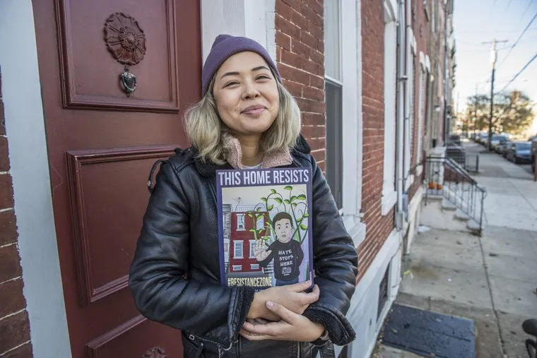 Erika Guadalupe Núñez holds the placard she created for South Philadelphia households to display to promote solidarity in the wake of ICE raids.