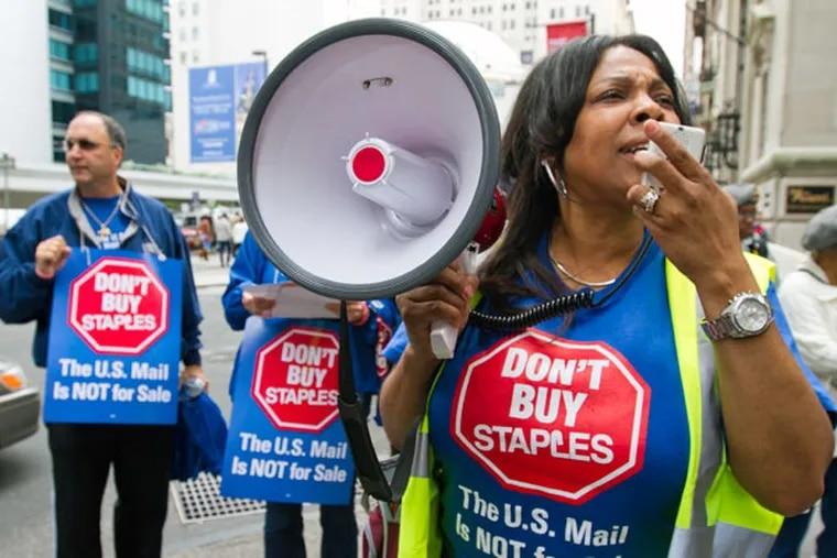Cindy Heyward, American Postal Workers Union Philadelphia local recording secretary, protests October 7, 2014. at 1500 Chestnut St. ( DAVID M WARREN / Staff Photographer )
