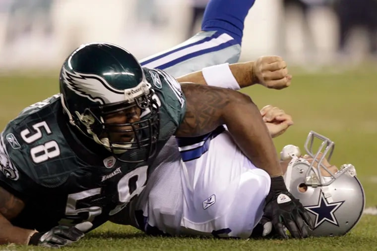 Eagles' Trent Cole takes down Dallas quarterback Tony Romo, who was sacked three times.