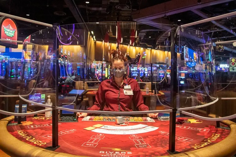 Morgan Sahm, a card dealer, awaits customers at a poker table surrounded by pandemic-era plastic shielding on the reopening day for the Rivers Casino Philadelphia on July 17.