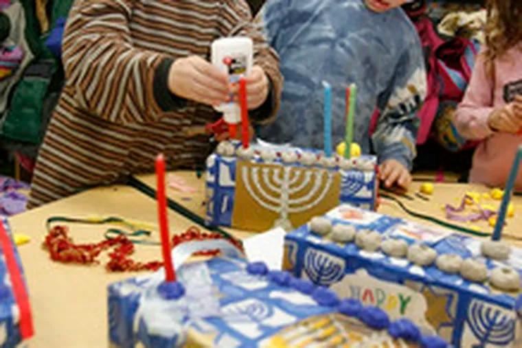 At the Katz Jewish Community Center in Cherry Hill, kindergartners Stav Bennie Katz (left) and Samuel Kilsdonk work on their eco-friendly menorahs.
