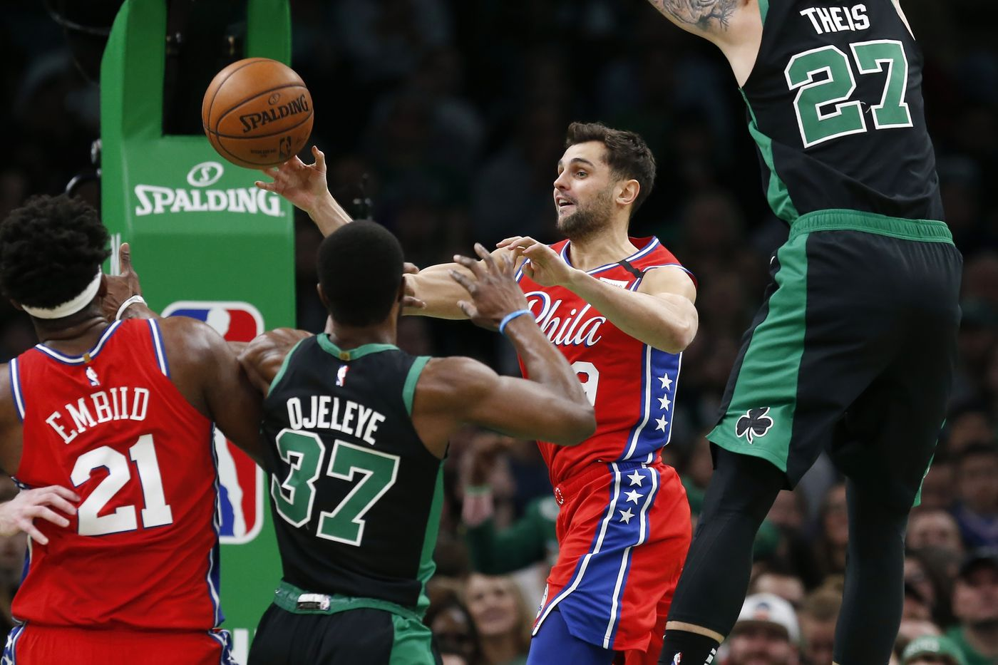 The Sixers' Raul Neto tries to pass out of a traffic jam in the lane during the first half.