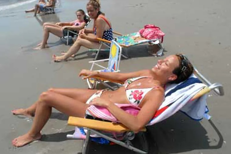 Nicole Murphy of Clifton Heights basks in the sun on the beach in Ocean City, N.J. She also uses indoor tanning salons. (April Saul / Staff)