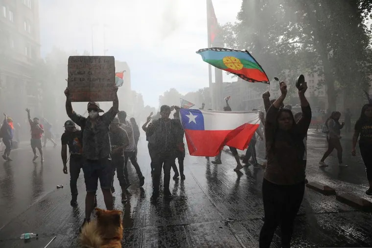 Anti-government demonstrators are sprayed by a police water cannon during a protest in Santiago, Chile, on Saturday.Chile has been facing days of unrest, triggered by a relatively minor increase in subway fares.