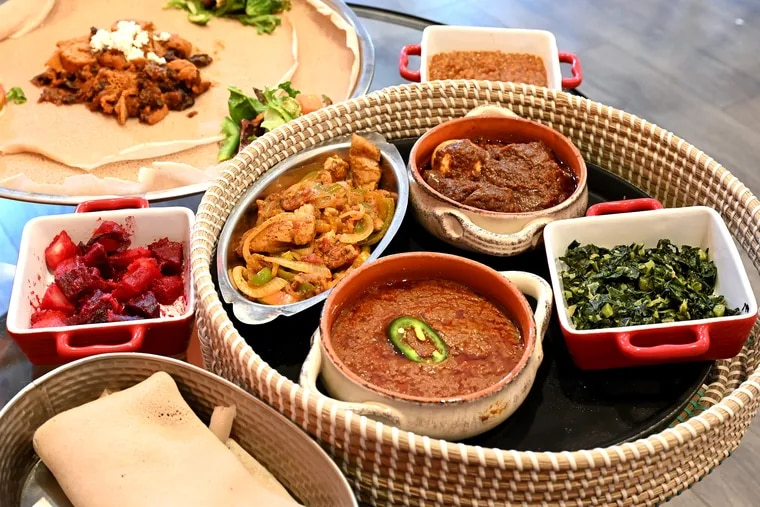 The injera combination platter at Buna Cafe in West Philadelphia July 28, 2021. Sides inside the round basket, clockwise from upper left are: Asa goulash; Doro wot; Gomen; and bozena shiro. Outside the basket, clockwise from lower left are injera bread (a spongy sour fermented flatbread); red beets and potatoes; quanta firfir and salad, resting on large Injera bread. and in rear, misir.