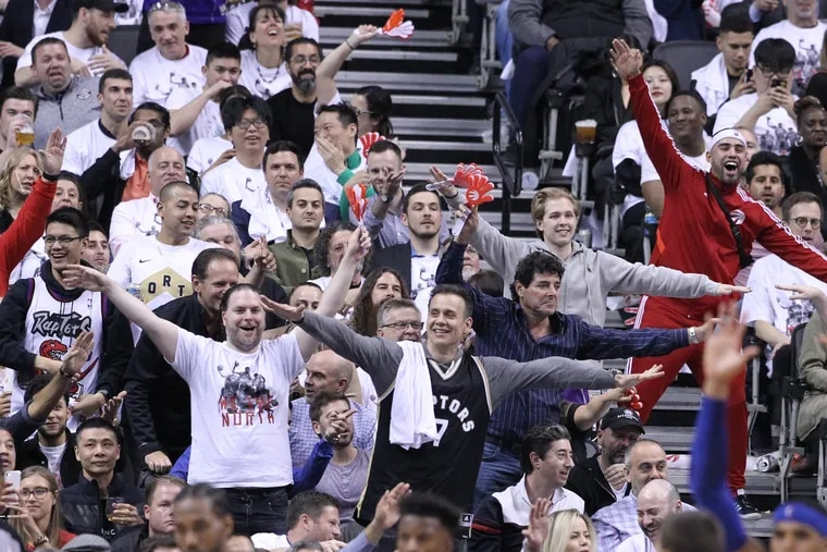 Raptor fans mock Joel Embiid for his flying celebration during game 3 of the series as he leaves their NBA Eastern Conference semifinal game at the Scotiabank Arena in Toronto on May 7, 2019.
