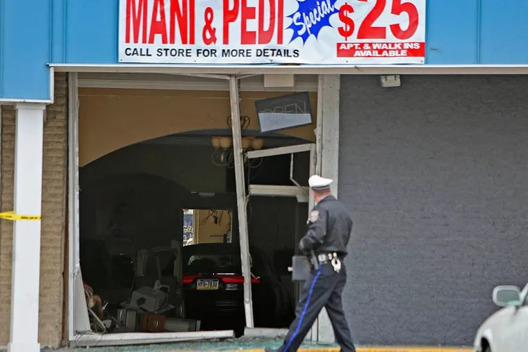 Police and L&I officials gather outside Cindy's Nail Salon on Mar. 31, 2015, in the Bustleton section of Philadelphia after a motorist drove into the shop. ( Joseph Kaczmarek / The Daily News and Inquirer )