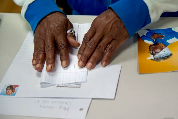 Darlene Harcum folds up a letter to her son during a Family Portrait and Letter Writing Day hosted by photographer Tyreek Dekeyser at the Village of Arts and Humanities.