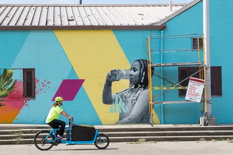 Drink More Tap, diseñado por el artista salvadoreño CALO Rosa, en el Centro de Recreación Narcisa Cruz. El mural presenta imágenes de residentes locales y aborda la desconfianza de la comunidad en el agua de la pluma.