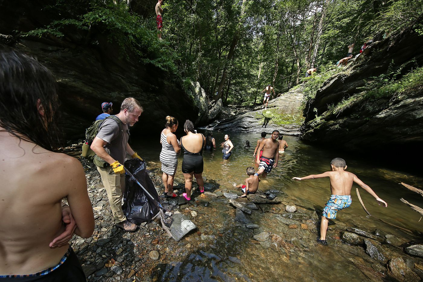 Shawn Green, at left, who is the volunteer manager for Friends of the Wissahickon, picks up litter as a crowd cools off at Devil's Pool in Wissahickon Valley Park in 2019.