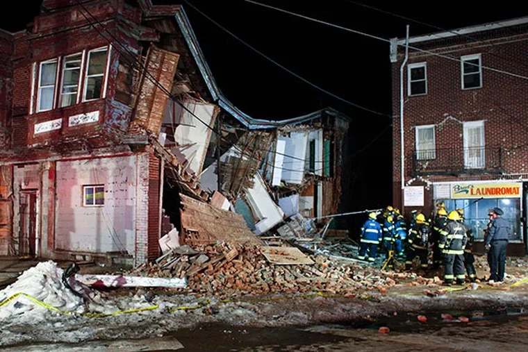 Firefighters use a pole to insert a listening device as they make sure no one is trapped in the debris after row house collapsed on Ogontz Avenue near Limekiln Pike in the East Germantown section of Philadelphia on Sunday, Feb. 23, 2014.  (For the Daily News/ Joseph Kaczmarek)