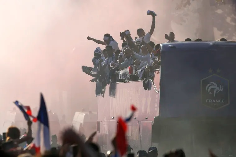 The crowd cheers France's victorious World Cup team descending in a bus upon Paris' packed Champs-Elysees avenue after the team's victory over Croatia.