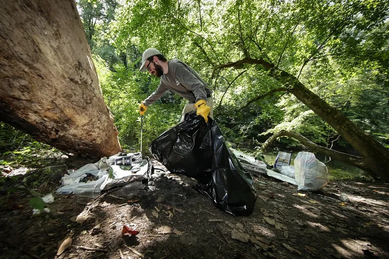 In summer 2019, Jordan Ostrum, who is part of the seasonal staff outreach team for Friends of the Wissahickon, cleaned up trash left behind at Wissahickon Valley Park in Philadelphia.