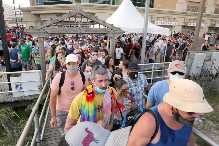 Fans enter the beach, many wearing masks, for the Phish beach concert, in Atlantic City, Friday, Aug. 13, 2021.