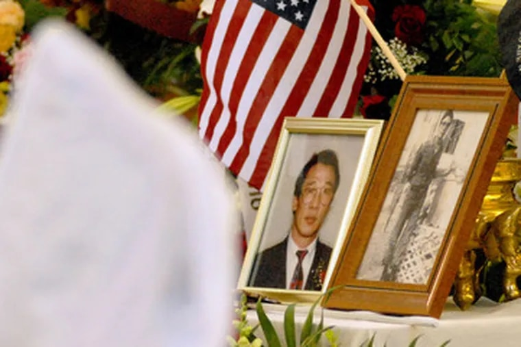 Photographs of Hoa Pham are displayed at his Funeral Massat St. Alice Roman Catholic Church in Upper Darby. The Mass for Pham, a South Vietnamese army veteran who worked fora Defense Department subcontractor, was said Nov. 15.