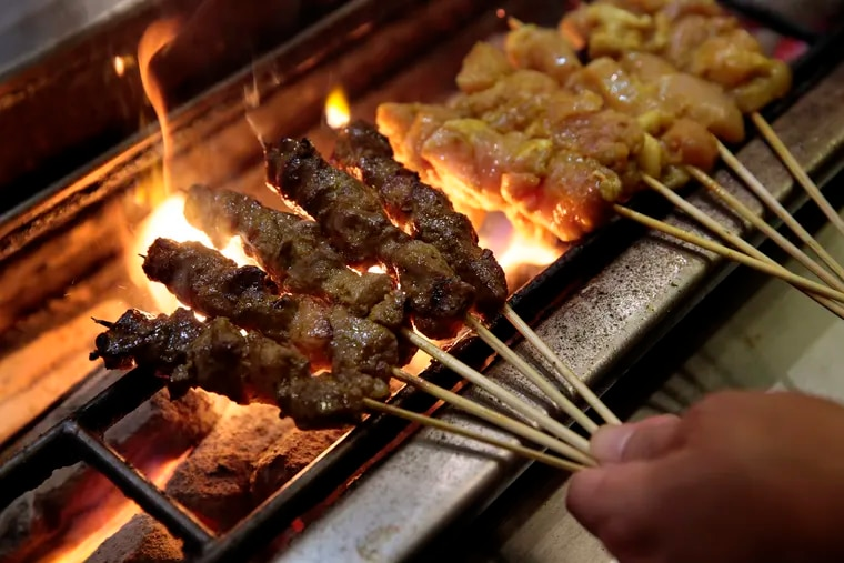 Goat (left) and chicken sate skewers being grilled at Sate Kampar, 1837 E. Passyunk Ave. in Philadelphia.