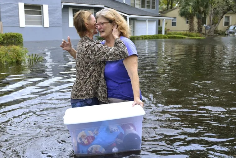 Charlotte Glaze gives Donna Lamb a teary hug as she floats out her belongings after Hurricane Irma passed Jacksonville, Fla.