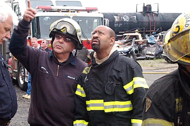 Mayor Nutter looks on as Fire Fighter Louis Brasted gives him instruction before entering a simulated building collapse. (David Kearney)