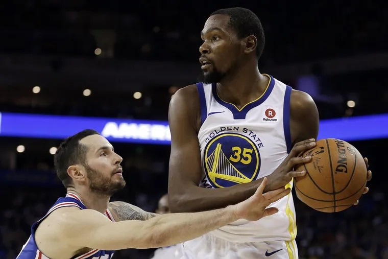 The Warriors' Kevin Durant (35) looks to pass away from 76ers defender  JJ Redick during the first half Saturday.