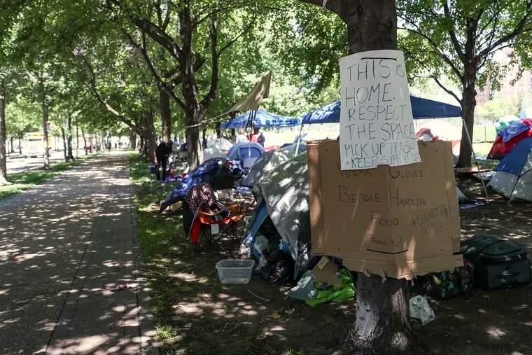 A sign hangs at the encampment set up at 22nd and Benjamin Franklin Parkway in Philadelphia on Friday, June 12, 2020. There is currently a community of homeless people and protesters living and volunteering there.