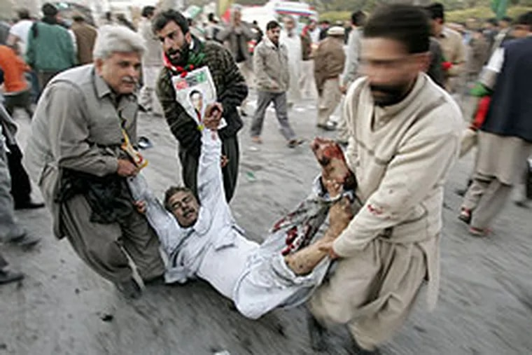 Volunteers carry an injured supporter of Pakistan former Prime Minister Benazir Bhutto after a suicide attack in Rawalpindi, Pakistan that killed Bhutto and at least 20 others.