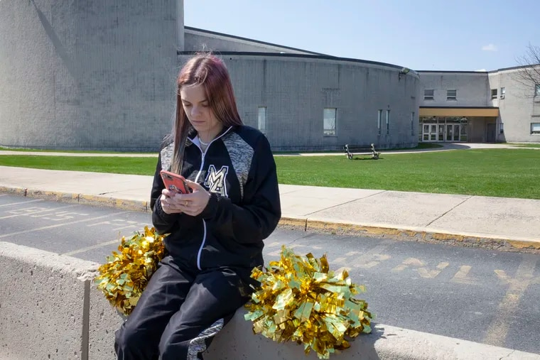Brandi Levy wears her former cheerleading outfit while sitting outside Mahanoy Area High School in Mahanoy City in April.
