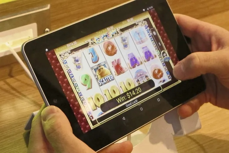 An employee at Resorts Casino Hotel in Atlantic City tries a touchscreen tablet device the day before the opening of the casino's internet gambling lounge in April 2015.
