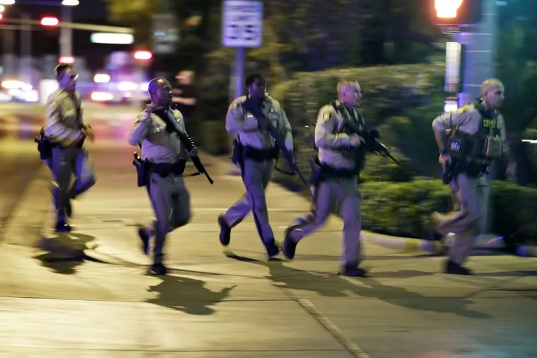 Police run to cover at the scene of the shooting near the Mandalay Bay Resort and Casino on the Las Vegas Strip.