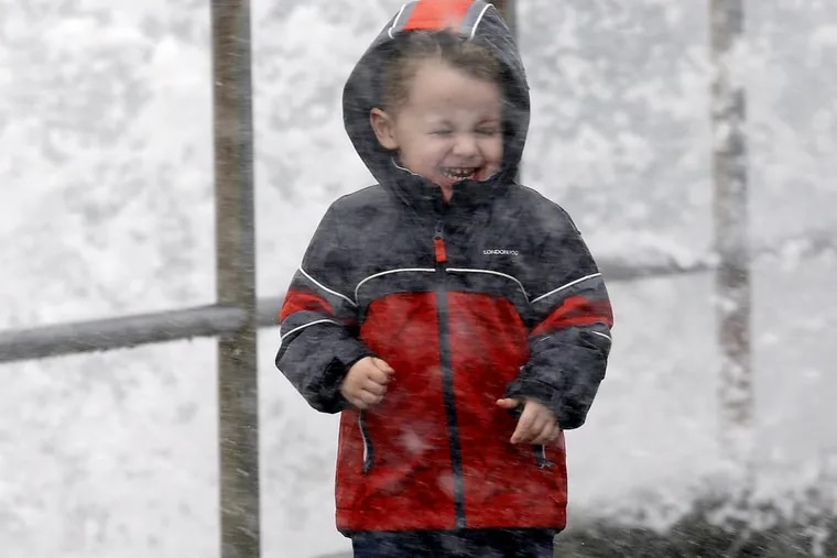 Archer Christiansen, 3, braces himself against wind and a breaking wave as he walks with his parents in a windstorm along the Puget Sound in Washington on Monday.