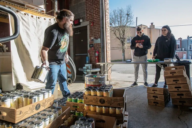 Steve Buller (left) a bartender at Tired Hands Brewing Company in Ardmore, grabs the beer selection for customers in March. Breweries and distillers are one of the many Pennsylvania industries that could benefit from the 2020 stimulus plan just passed in Congress.