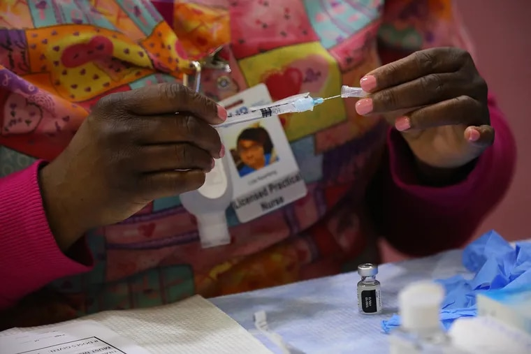 A health-care worker prepares a vaccine dose at a community COVID-19 vaccination clinic run by the Philadelphia Department of Public Health at University of the Sciences' Bobby Morgan Arena in West Philadelphia in February.
