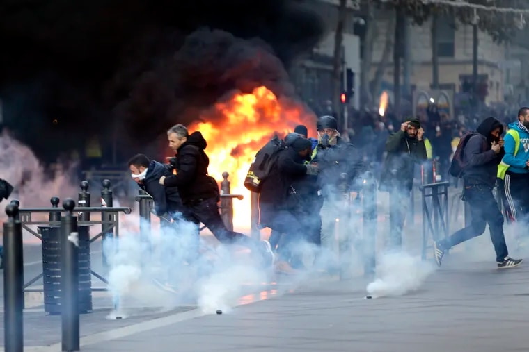 People run away from a burning car during clashes, Saturday, Dec. 8, 2018 in Marseille, southern France. The grassroots movement began as resistance against a rise in taxes for diesel and gasoline, but quickly expanded to encompass frustration at stagnant incomes and the growing cost of living.
