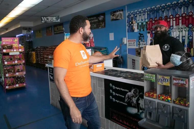 Keny Núñez (izquierda) de Delivery Guys entrega comida de Sabor Rico Bakery a un empleado de Mercado Pet Supplies en Filadelfia, el jueves 22 de julio de 2021.