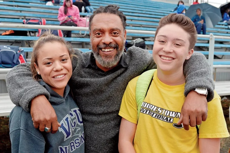 Matt Dawkins (right) hangs out with twin sister Jada Dawkins and their father, Nigel Dawkins, during a meet at Washington Township High School on April 14, 2015.